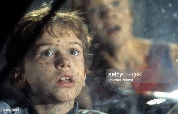 Joseph Mazzello and Ariana Richards look out a window in a scene from the film 'Jurassic Park' 1993