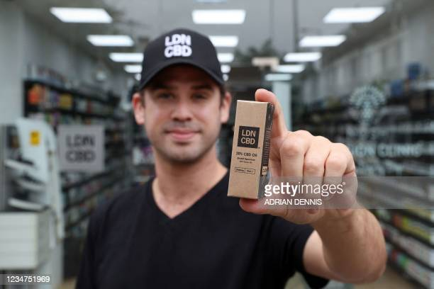 Joseph Oliver, CEO of British-based cannabidiol firm LDN CBD, poses outside Chelsea Health store in London on August 16, 2021. - Britain's legal...