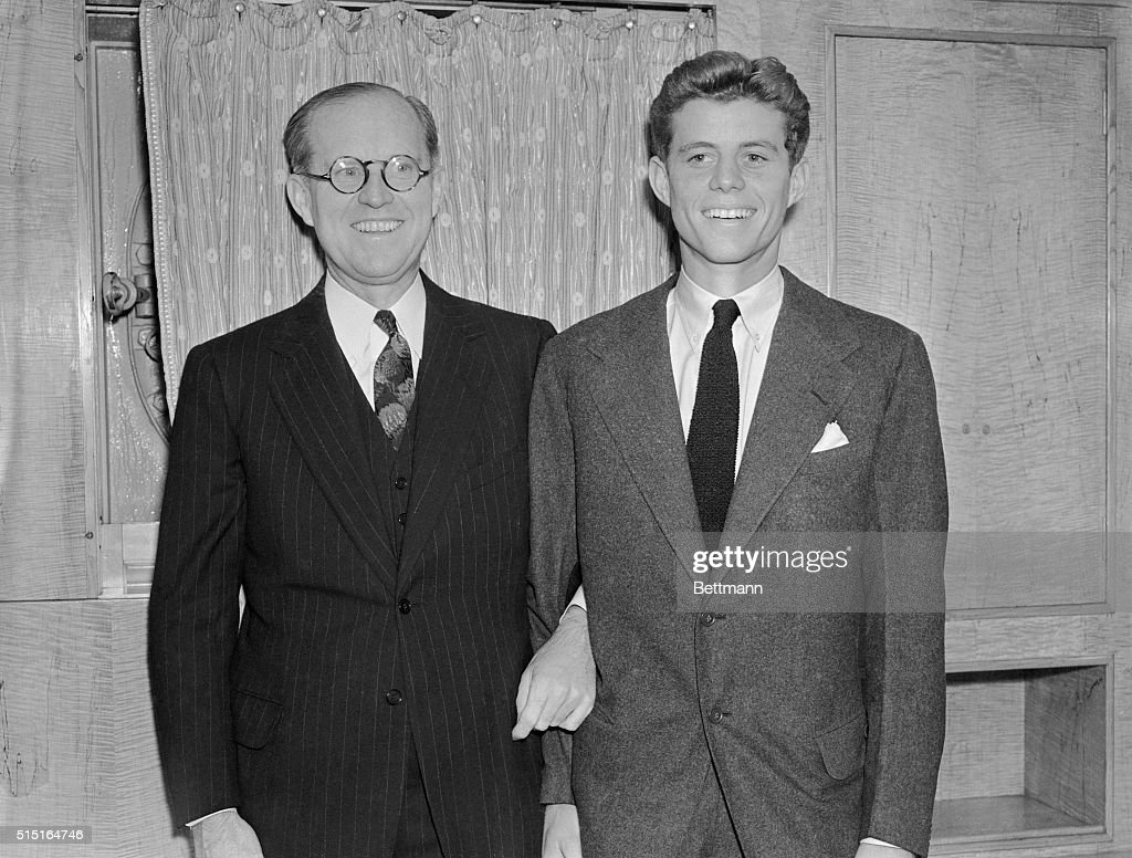 Joseph P. Kennedy, U.S. Ambassador to Great Britain (L), poses for newspapermen when he arrived on the S.S. Queen Mary. He is 'not', he said, 'particularly optimistic about peace in Europe.' With him is his son, John Kennedy, who went down the bay to meet him on board ship.