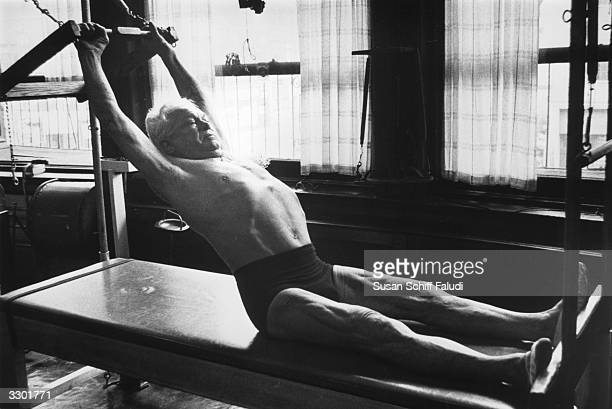 Joseph Pilates inventor and promoter of the Pilates fitness method exercising at his 8th Avenue studio in New York City circa 1960 He is using a...