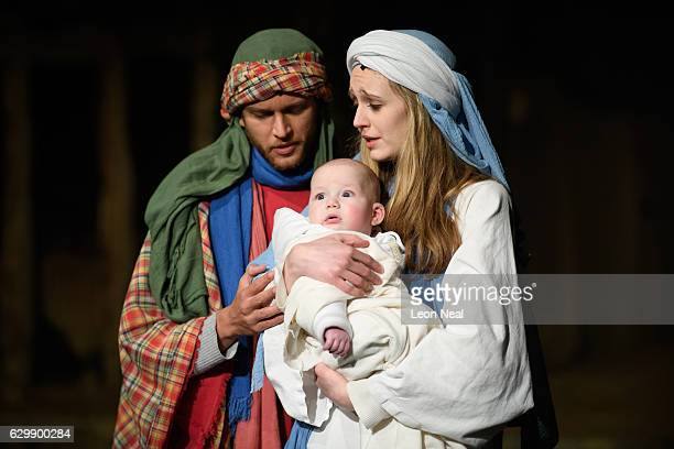 Joseph played by Liam Driver and Mary played by Rachel Burdon hold the Baby Jesus played by Jasper CravenSmith stand onstage during a performance of...
