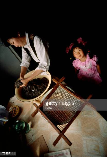 Joseph Popovitch's wife salts the caviar of a freshly killed sturgeon inside her house whilst her granddaughter watches in Amur Delta's region off...