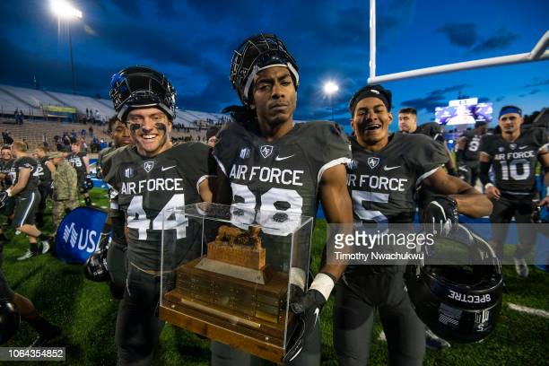 Joseph Saucier of the Air Force Falcons center walks with the RamFalcon trophy after defeating the Colorado State Rams at Falcon Stadium on November...