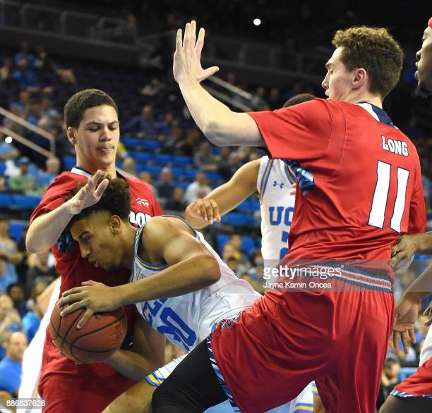 Joseph Wallace of the UCLA Bruins along with DeShawndre Black and Cole Long of the Detroit Mercy Titans battle for a rebound in the second half of...