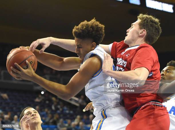 Joseph Wallace of the UCLA Bruins and Cole Long of the Detroit Mercy Titans battle for a rebound in the second half of the game at Pauley Pavilion on...