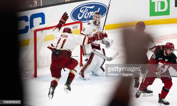 Joseph Woll of the Boston College Eagles celebrates an Eagles win against the Harvard Crimson with teammate Jack McBain during NCAA hockey in the...