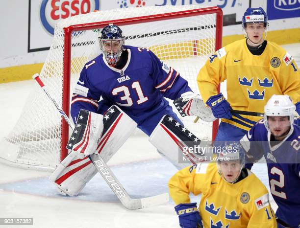Joseph Woll of United States looks around Elias Pettersson of Sweden to locate the puck during the first period of play in the IIHF World Junior...