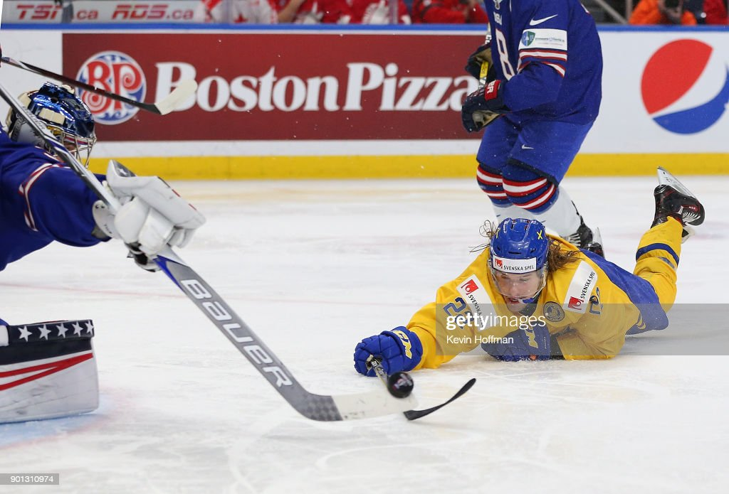 Joseph Woll #31 of United States pokes the puck away from Axel Jonsson Fjllby #22 of Sweden in the third period during the IIHF World Junior Championship at KeyBank Center on January 4, 2018 in Buffalo, New York. Sweden beat the United States 4-2.