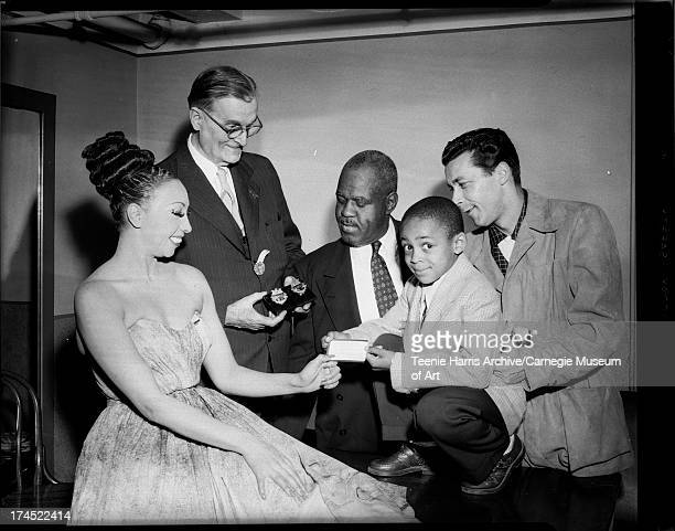 Josephine Baker accepting Hill City membership card from Leslie Powell with George Fairley holding police badges honoring Dean Martin and Jerry Lewis...