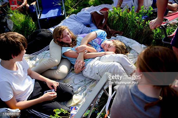 Josephine Maalouf of New Delhi India second from left lays on a blanket with Claire Beaulieu of Warrenton VA second from right while Beaulieu's...