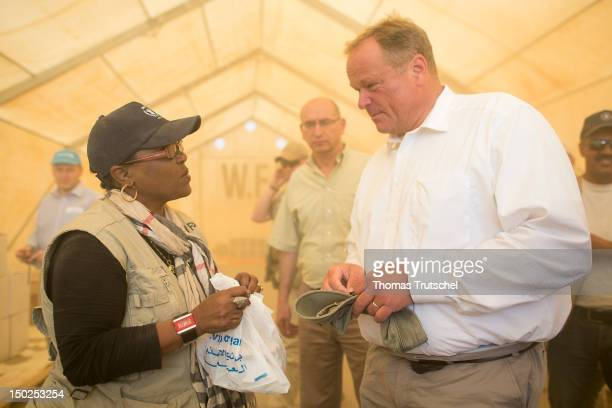 Josephine MahgiaJanabi of UNHCR shows a bag with food for the refugees to German Minister for Development Dirk Niebel as he visits UNHCR camp Zaatari...