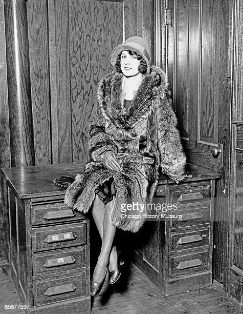 Josephine Simard who said she was the wife of gangster Hymie Weiss wearing a fur coat sitting on a wooden desk in a room in Chicago Illinois 1927 A...