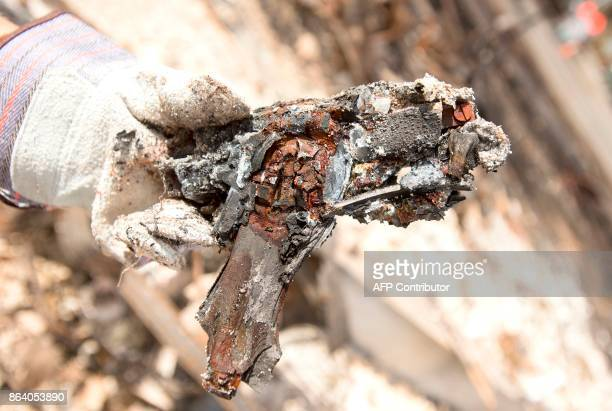 Josette Lushenko holds up a burned hand gun she found while searching through the remains of the property where her sister Karen Aycock died during...