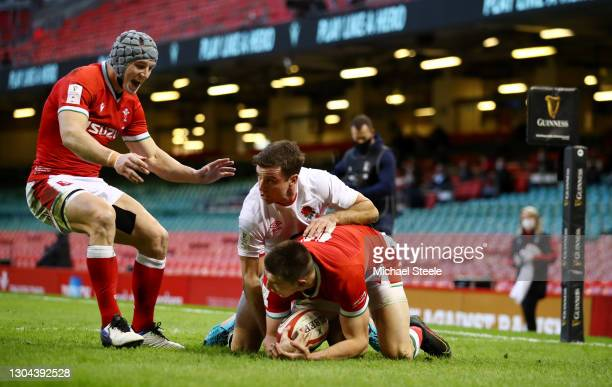 Josh Adams of Wales beats George Ford of England to score their side's first try as Jonathan Davies celebrates during the Guinness Six Nations match...