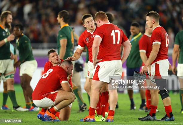 Josh Adams of Wales consults teammate Dillon Lewis as they react after defeat in the Rugby World Cup 2019 Semi-Final match between Wales and South...