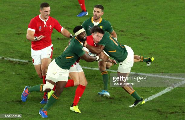 Josh Adams of Wales is high tackled by Makazole Mapimpi of South Africa and Siya Kolisi of South Africa during the Rugby World Cup 2019 Semi-Final...