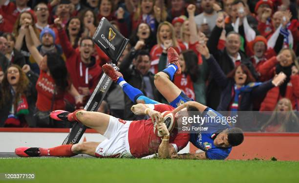 Josh Adams of Wales scores his sides first try as he is challenged by Tommaso Allan of Italy during the 2020 Guinness Six Nations match between Wales...
