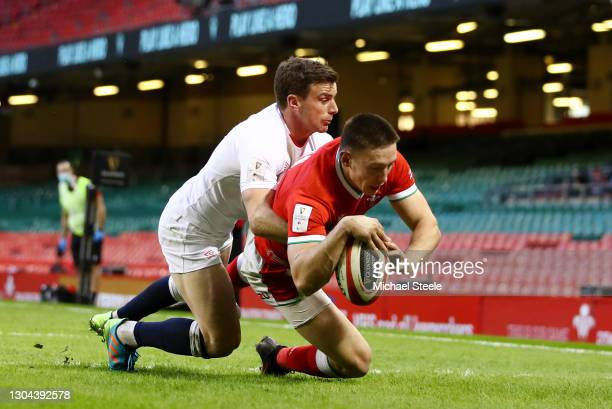 Josh Adams of Wales scores their side's first try as George Ford of England tackles during the Guinness Six Nations match between Wales and England...