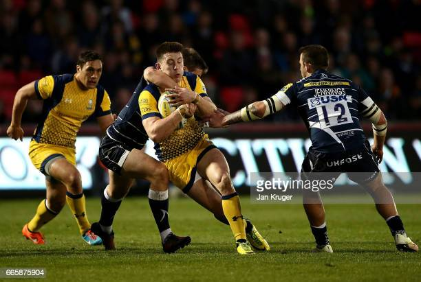 Josh Adams of Worcester Warriors is tackled by Alan MacGinty of Sale Sharks during the Aviva Premiership match between Sale Sharks and Worcester...