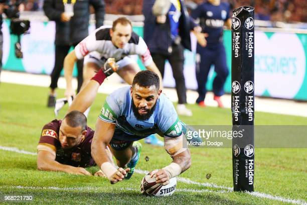 Josh AddoCarr of the Blues scores a try past Will Chamers of the Maroons during game one of the State Of Origin series between the Queensland Maroons...