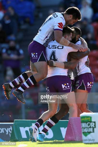 Josh AddoCarr of the Storm celebrates his try with team mates during the round 15 NRL match between the Newcastle Knights and the Melbourne Storm at...