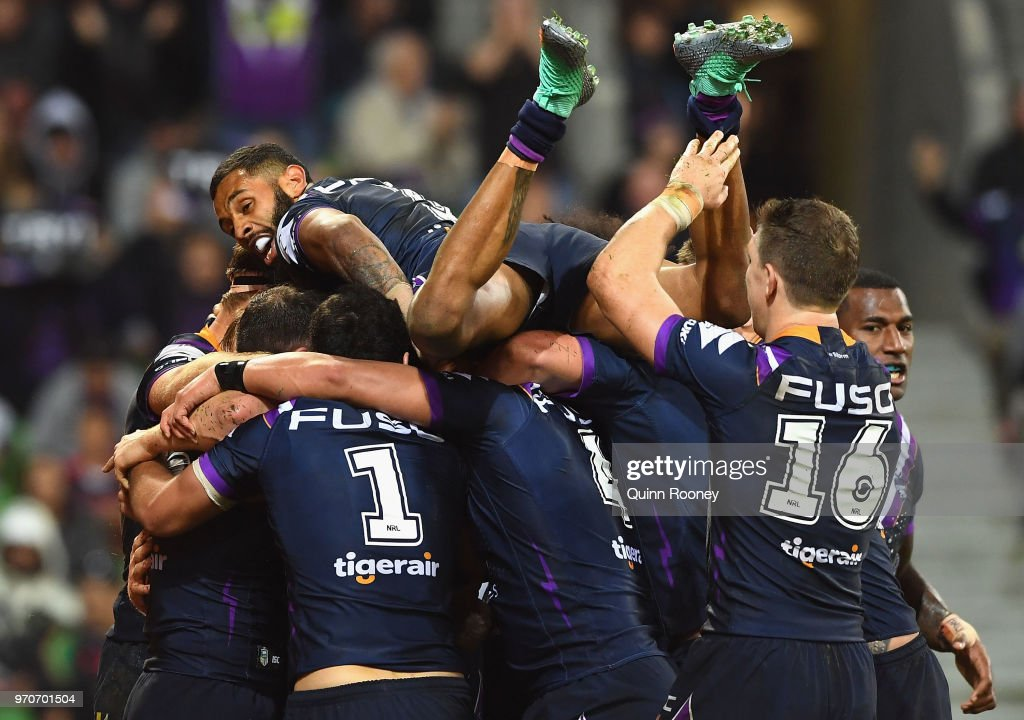 Josh Addo-Carr of the Storm jumps on top of his Storm team mates as they celebrate a try by Cameron Munster during the round 14 NRL match between the Melbourne Storm and the Brisbane Broncos at AAMI Park on June 10, 2018 in Melbourne, Australia.