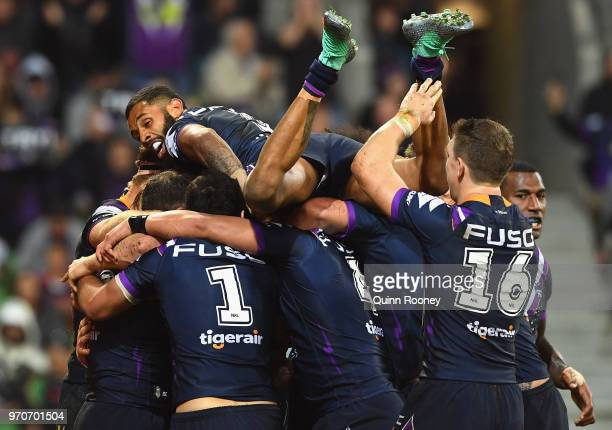 Josh AddoCarr of the Storm jumps on top of his Storm team mates as they celebrate a try by Cameron Munster during the round 14 NRL match between the...