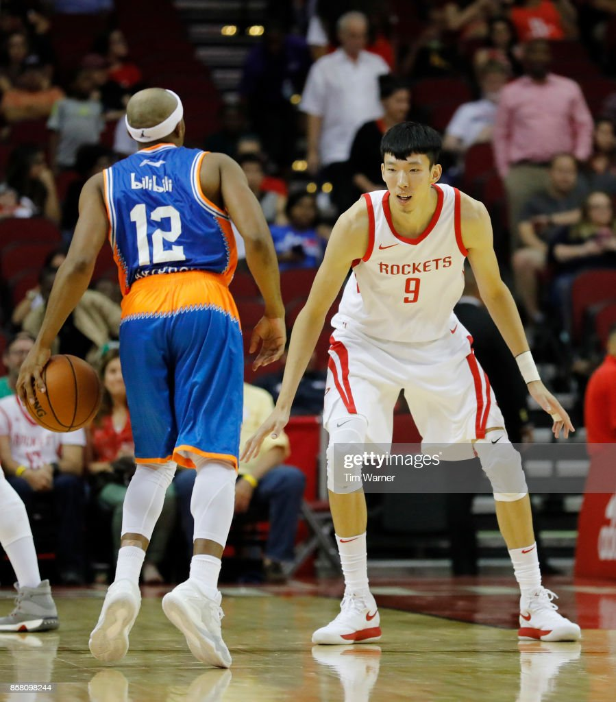 Josh Akognon #12 of Shanghai Sharks controls the ball defended by Zhou Qi #9 of Houston Rockets in the second quarter at Toyota Center on October 5, 2017 in Houston, Texas.