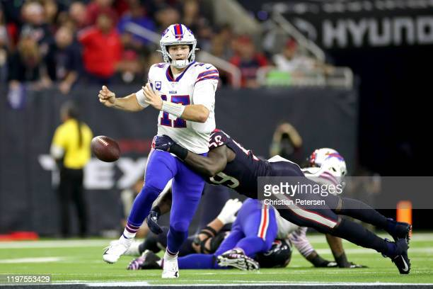 Josh Allen of the Buffalo Bills fumbles the ball as he is hit by Whitney Mercilus of the Houston Texans during the fourth quarter of the AFC Wild...