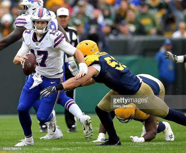 Josh Allen of the Buffalo Bills runs past Kyler Fackrell of the Green Bay Packers during the third quarter of a game at Lambeau Field on September 30...