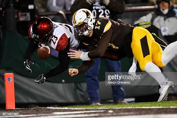 Josh Allen of the Wyoming Cowboys forces a fumble that resulted in a touchback after throwing an interception to Damontae Kazee of the San Diego...