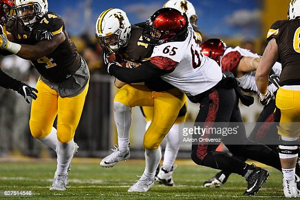 Josh Allen of the Wyoming Cowboys scrambles and is stopped by Sergio Phillips of the San Diego State Aztecs during the second half of San Diego...
