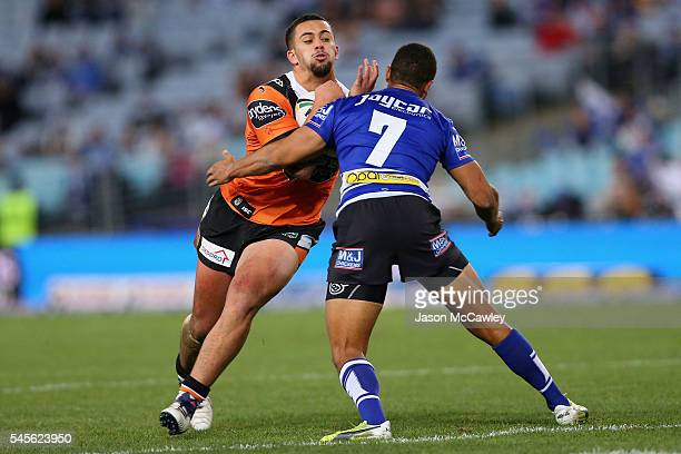Josh Aloiai of the Tigers is tackled by Moses Mbye of the Bulldogs during the round 18 NRL match between the Canterbury Bulldogs and the Wests Tigers...