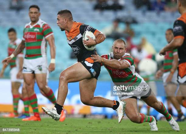 Josh Aloiai of the Tigers is tackled during the round one NRL match between the South Sydney Rabbitohs and the Wests Tigers at ANZ Stadium on March 3...
