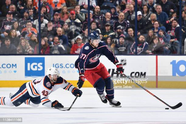 Josh Anderson of the Columbus Blue Jackets attempts to keep the puck from Josh Currie of the Edmonton Oilers during the first period of a game on...