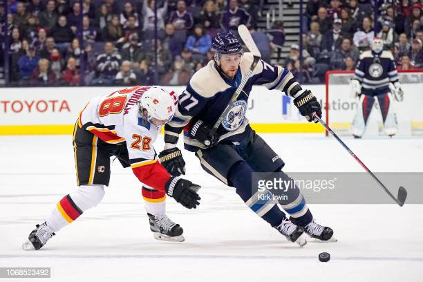 Josh Anderson of the Columbus Blue Jackets attempts to skate the puck past Elias Lindholm of the Calgary Flames during the second period on December...