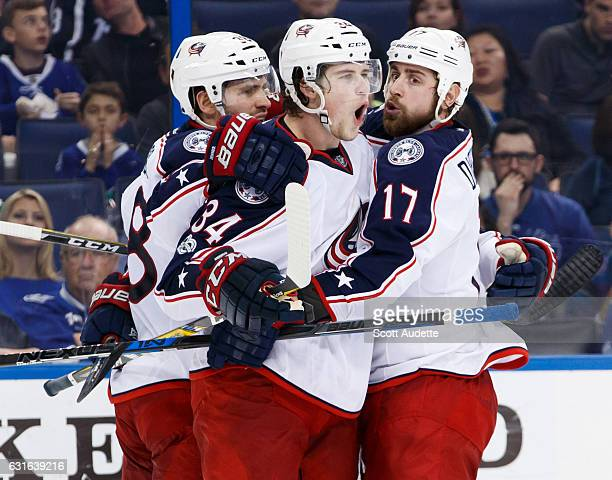 Josh Anderson of the Columbus Blue Jackets celebrates a goal with teammates Boone Jenner and Brandon Dubinsky against the Tampa Bay Lightning during...