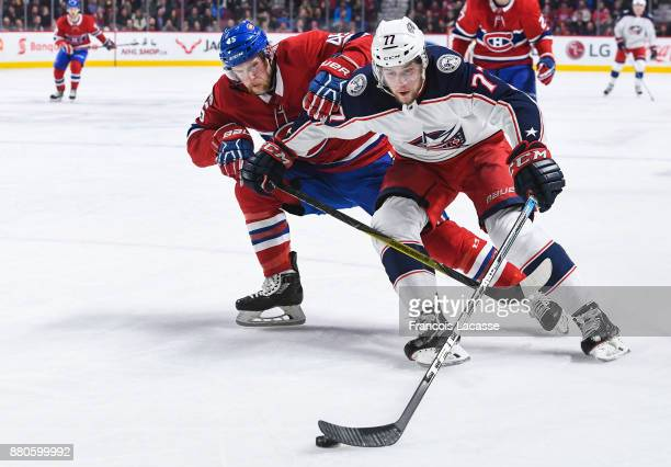 Josh Anderson of the Columbus Blue Jackets controls the puck while being challenged by Joe Morrow of the Montreal Canadiens in the NHL game at the...