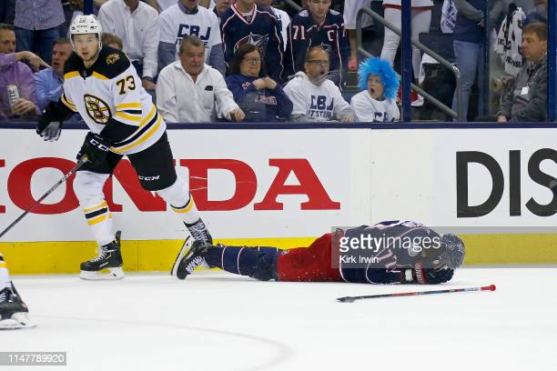 Josh Anderson of the Columbus Blue Jackets lays on the ice after being checked in the head by Charlie McAvoy of the Boston Bruins in Game Six of the...