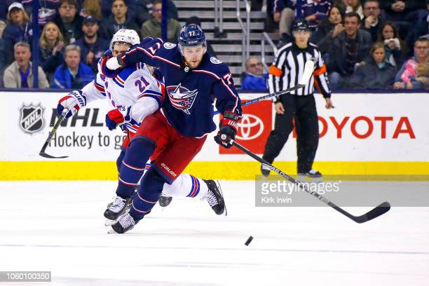 Josh Anderson of the Columbus Blue Jackets pushes away Brett Howden of the New York Rangers while chasing after the puck during the overtime period...