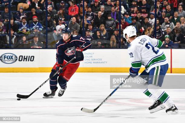 Josh Anderson of the Columbus Blue Jackets skates with the puck as Daniel Sedin of the Vancouver Canucks defends during the first period of a game on...