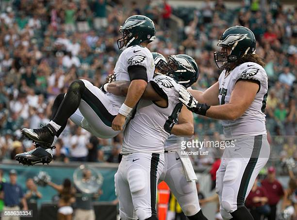 Josh Andrews of the Philadelphia Eagles picks up Chase Daniel after he ran for a touchdown in the first quarter against the Tampa Bay Buccaneers at...
