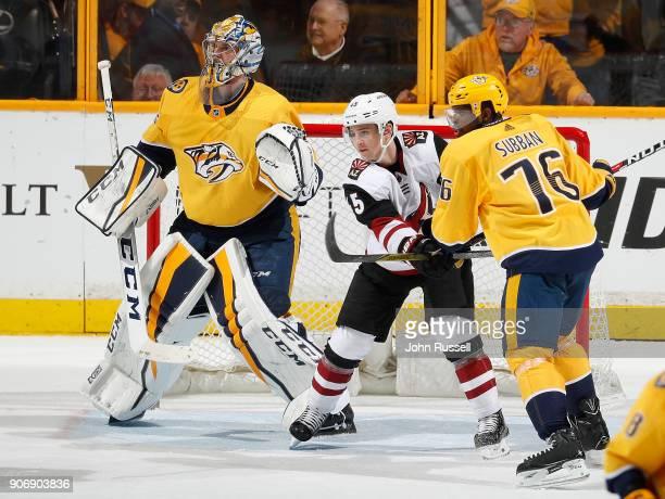 Josh Archibald of the Arizona Coyotes battles between Pekka Rinne and PK Subban of the Nashville Predators during an NHL game at Bridgestone Arena on...