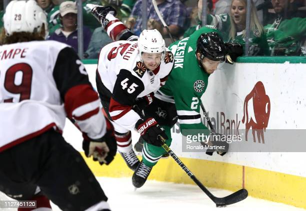 Josh Archibald of the Arizona Coyotes checks Jamie Oleksiak of the Dallas Stars into the boards in the second period at American Airlines Center on...