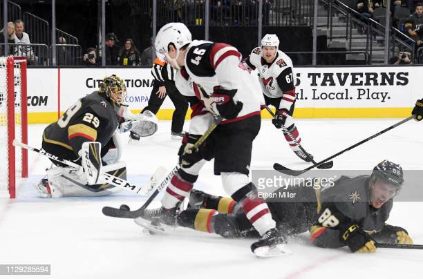 Josh Archibald of the Arizona Coyotes scores a thirdperiod goal against MarcAndre Fleury and Nate Schmidt of the Vegas Golden Knights during their...