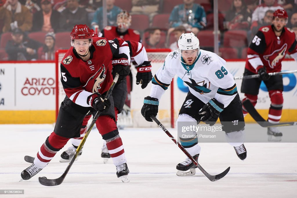 Josh Archibald #45 of the Arizona Coyotes skates with the puck ahead of Mikkel Boedker #89 of the San Jose Sharks during the first period of the NHL game at Gila River Arena on January 16, 2018 in Glendale, Arizona.