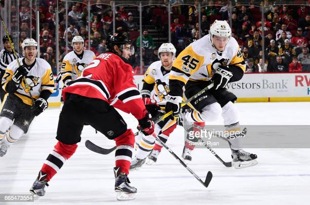 Josh Archibald of the Pittsburgh Penguins jumps to avoid the stick of John Moore of the New Jersey Devils during an NHL game at Prudential Center on...