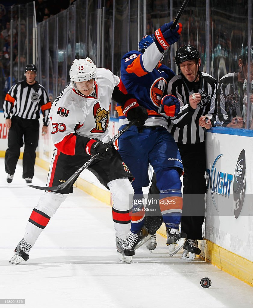 Josh Bailey #12 of the New York Islanders and linesman Brad Kovachik #71 are checked into the boards by Jakob Silfverberg #33 of the Ottawa Senators at Nassau Veterans Memorial Coliseum on March 3, 2013 in Uniondale, New York. The Islanders defeated the Senators 3-2 in a shootout.