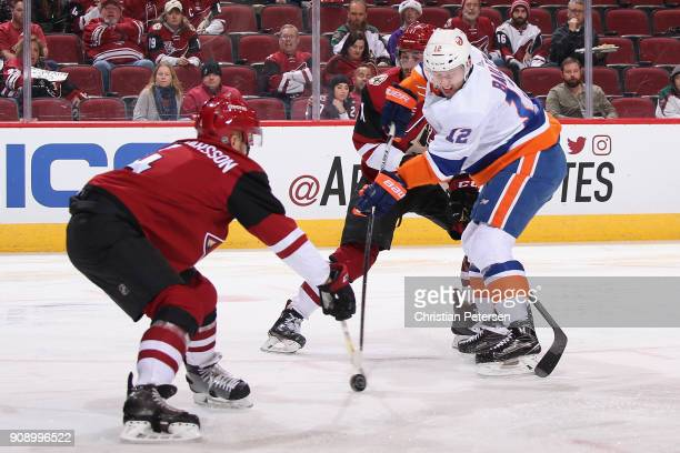 Josh Bailey of the New York Islanders attempts a shot past Niklas Hjalmarsson and Brendan Perlini of the Arizona Coyotes during the second period of...