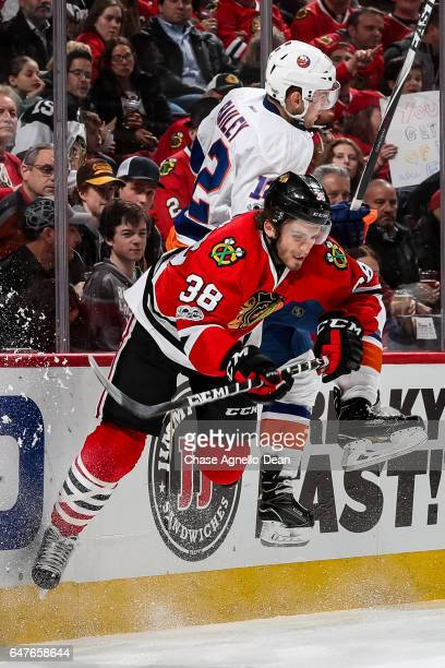 Josh Bailey of the New York Islanders checks Ryan Hartman of the Chicago Blackhawks in the second period at the United Center on March 3 2017 in...
